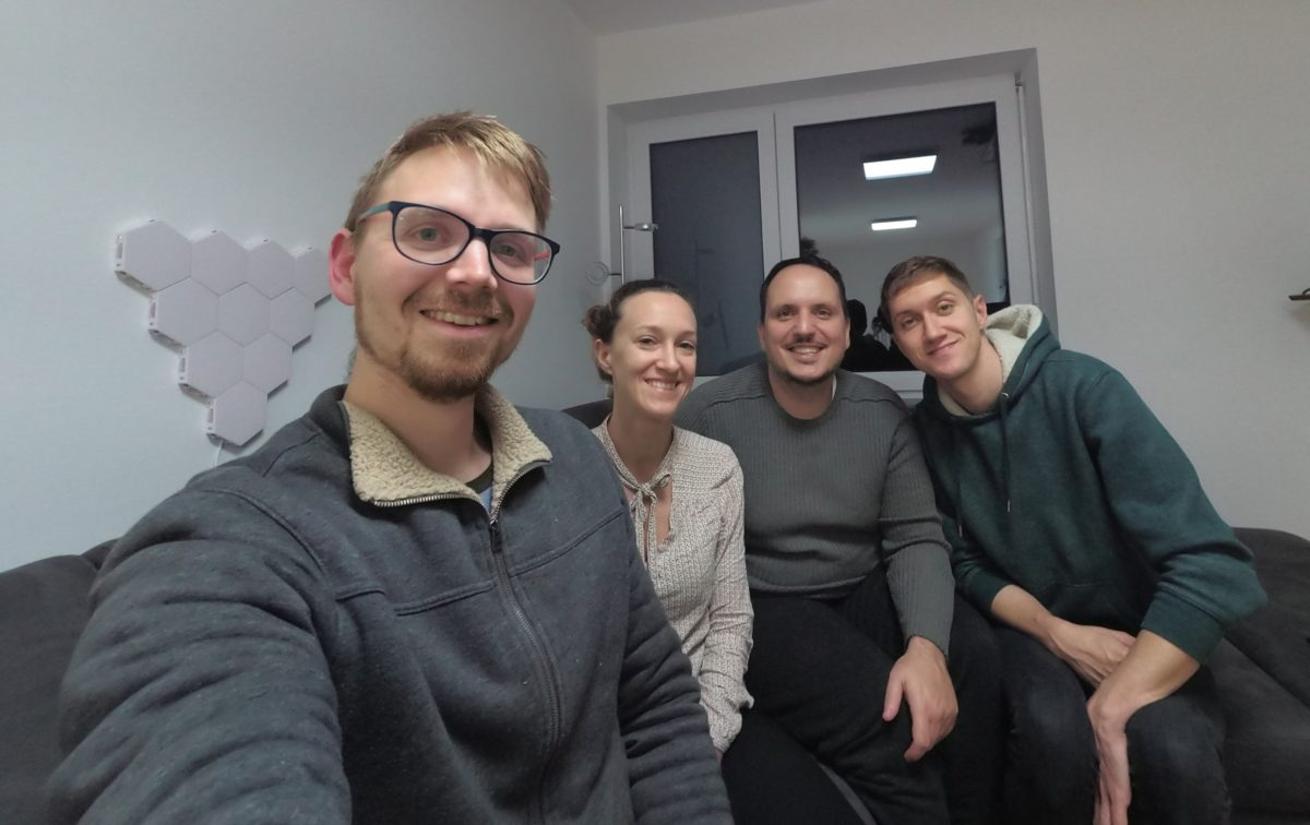 Team, 3 men, 1 woman, sitting in a room on a sofa