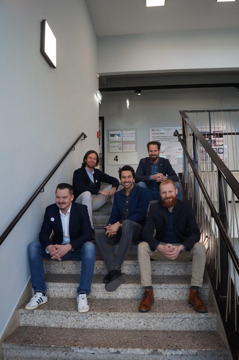 5 junge Männer, die auf den Stiegen eines Stiegenhauses einer Universität sitzen.