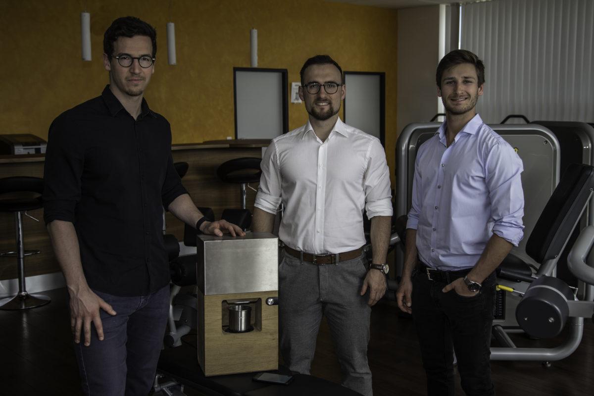 Drei junge Männer, die Gründer von Scalento, in einem Fitnessstudio, präsentieren ihr Produkt.