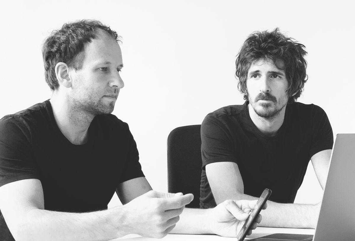 Zwei junge Männer mit Smartphone Inder Hand an einem Schreibtisch in dunklen T-Shirts, schwarz/weiß Foto