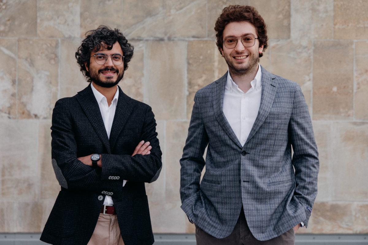 Zwei junge Männer, die Gründer,  mit dunklen Haaren und Brillen in Sakko vor einer Wand im Außenbereich