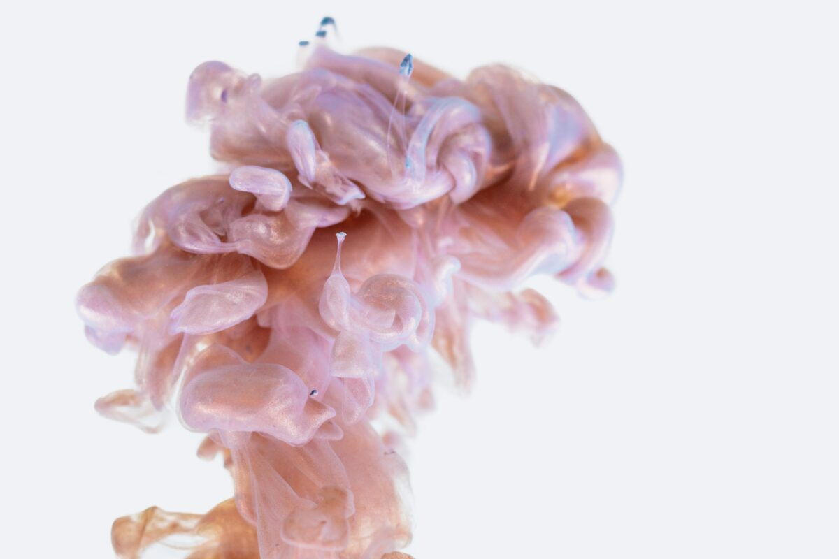 Pink color splashing and dissolving in water looking like the shape of a brain