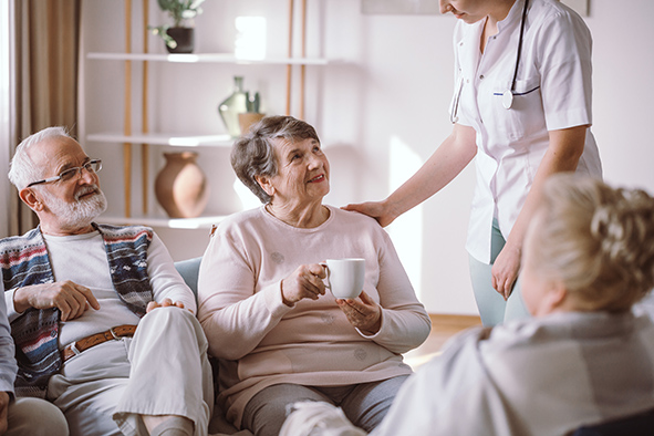 Senior lady talking with nurse and sitting with her elderly friends