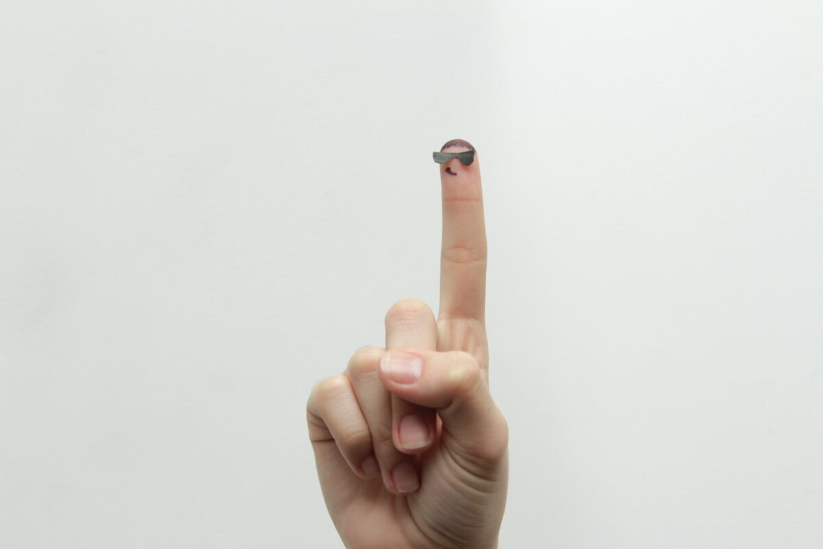 hand with raised finger on white background. Fingertip is wearing glasses and smiling.