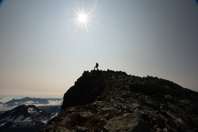 picture of man walking on the rim of a mountain and sun shining brightly