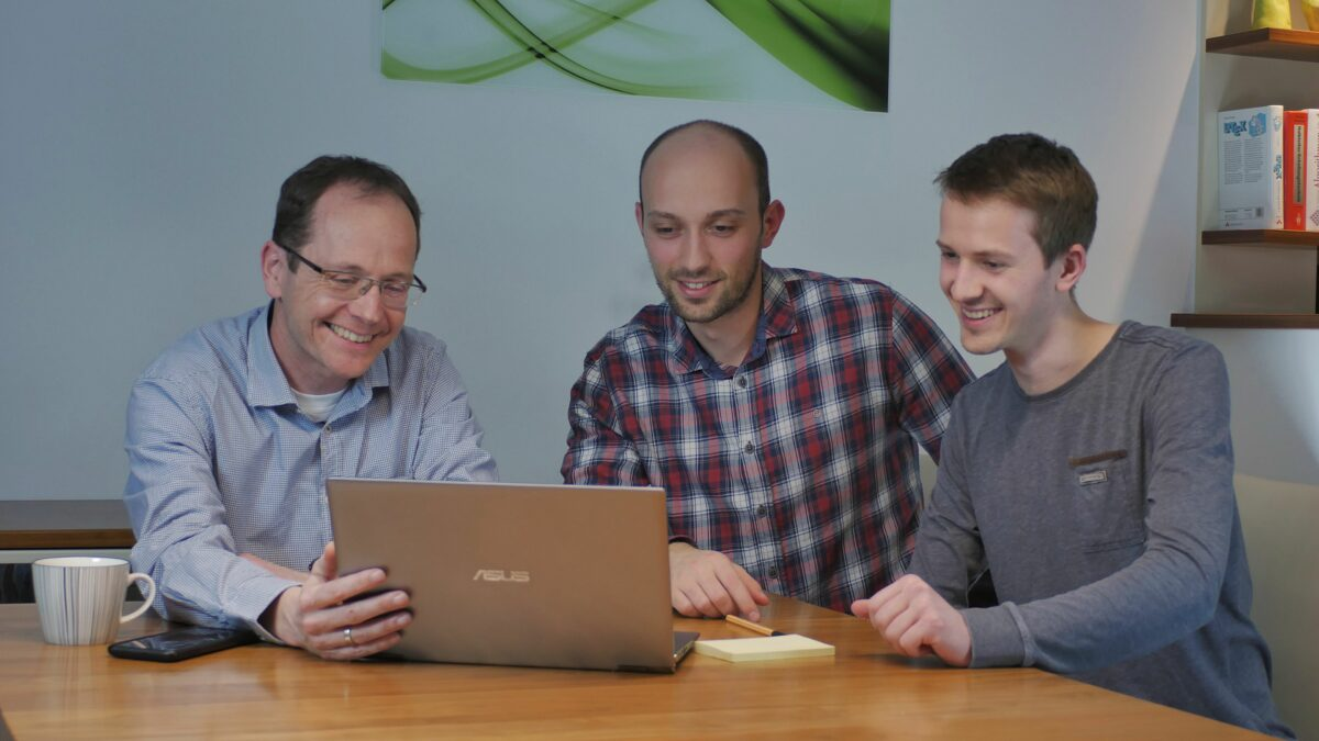3 men sitting at a table looking at a laptop
