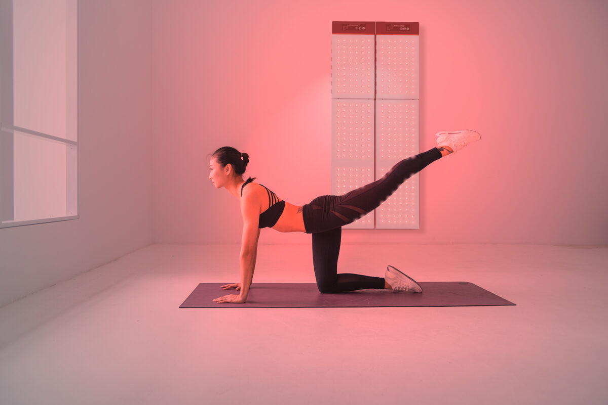 Young woman in Yoga position in front of the product, luminous red, panels hung up on the wall